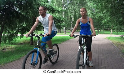 Relaxing Together - Couple approaching camera on bikes...