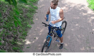Refreshing Drink - High angle of cyclist drinking from...