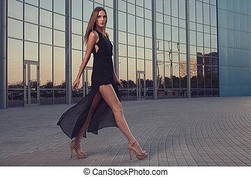 Walking woman in long black dress