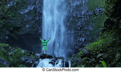 Man standing under large waterfall