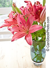 Fresh pink lilies in a blue glass vase