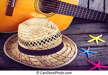 Acoustic guitar star hat and starfish on a grunge wood...