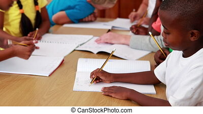 Pupils drawing in notepads during class in elementary school