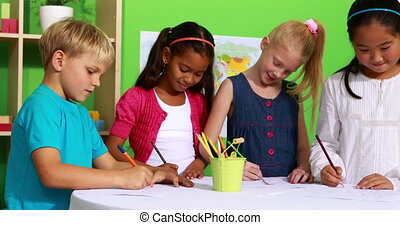 Cute classmates drawing at table together in playschool