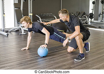 Strengthen arm muscles - Personal trainer working with young...