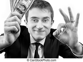 Businessman showing fan of money and sign OK