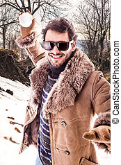 Snow battle - a young man wearing a sheepskin coat playing...