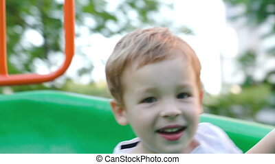 Happy child on slide outdoor - Happy little boy riding a...