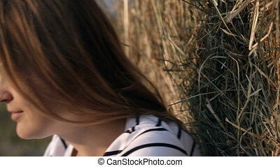 Smiling woman by the hay roll in field - Dolly close-up shot...