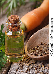 essential oil of carrot seeds in a bottle on a table...
