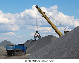 bucket loading in a truck and a big pile of gravel gray...