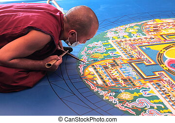 Tibetian monks constructing mandala from colored sand -...