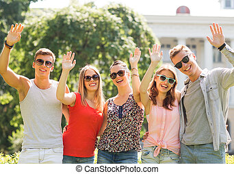 group of smiling friends waving hands outdoors - friendship,...