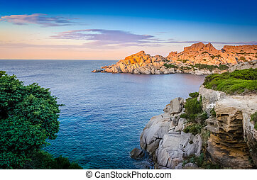 Ocean rocky coastline colorful sunset view, Sardinia, Italy