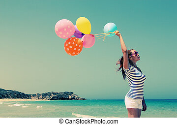 beautiful woman with colorful balloons on seaside