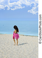 lonely girl walking on the beach near the sea with a red...