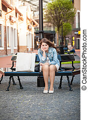 sad woman sitting on bench with shopping paper bag - Outdoor...