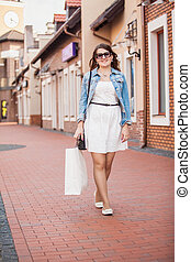 woman having shopping and walking on old street
