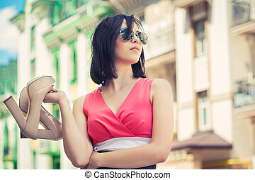 beautiful young woman holding a pair of shoes on a city...