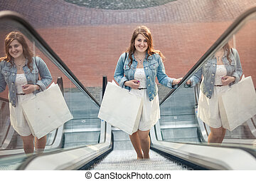 shopping woman in shopping mall on escalator