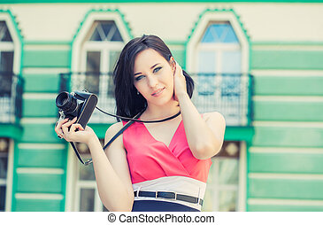 beautiful young woman taking photos with vintage camera on a...