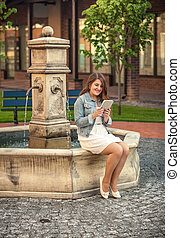 beautiful woman reading book on tablet on side of fountain -...