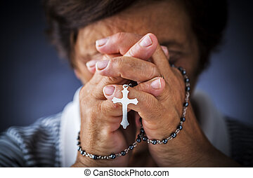 Praying with a rosary - Old woman with a rosary