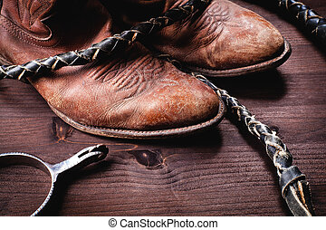 Cowboy boots whip and spurs on wood - vintage setting with...