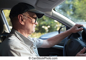 Senior man at the wheel - Side view of an elderly man in...