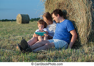Family of three with pad in the field with hay rolls