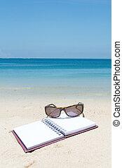 Beach summer time,book sunglass on white sand beach