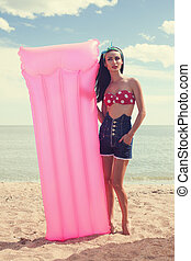 Stylish pinup girl posing with swimming mattress