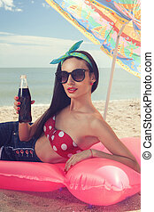 Fashionable model lying on mattress and drinking drink