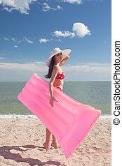 Stylish pinup girl posing with swimming mattress