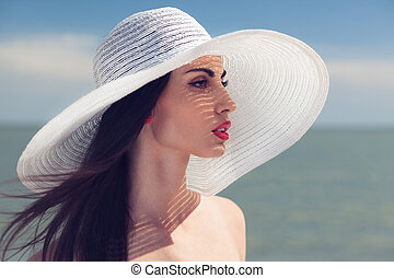 Closeup portrait of woman in big white hat