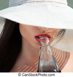 Closeup of beautiful woman in hat drinking drink