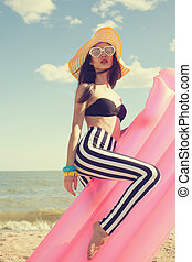 Fashionable woman in stylish swimsuit on beach