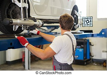 Young serviceman checking wheel alignment in a car workshop...