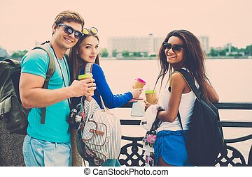 Multi-ethnic friends tourists with map and coffee cups near...
