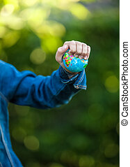 ittle girl squeezing Earth globe at hand - Closeup shot of...