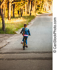 brunette girl riding bicycle on road at forest at sunset