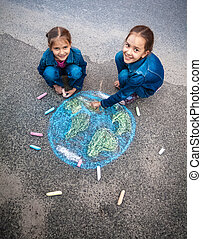 smiling girls drawing Earth with chalks on street - Two...