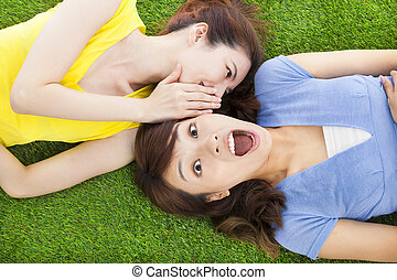 sisters whispering on the meadow and surprised expression