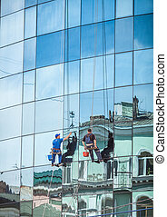 professional washers cleaning glass facade of skyscraper -...