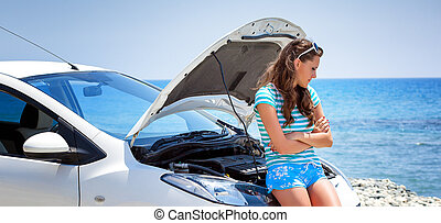 Woman is standing near broken car - Young brunette woman is...