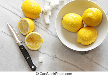 Fresh lemons and sugar cubes on marble counter top