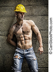 Handsome construction worker standing shirtless in front of...
