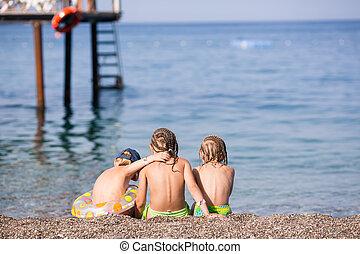 Three children sitting on a beach