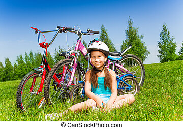 Small girl in blue shirt sits on a meadow with three...