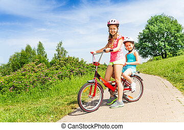 Two little girls sit on a bicycle